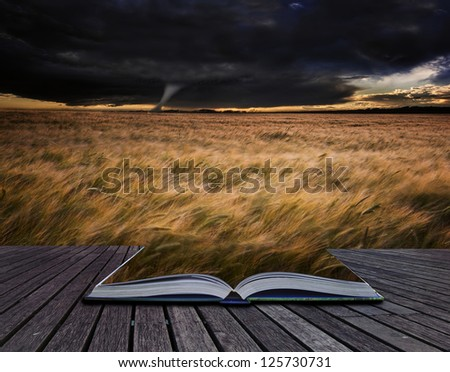 Creative concept image of stormy skies over Summer landscape in pages of book - stock photo