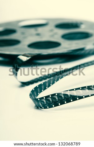 Creative concept of a retro movie film with a vintage film reel - stock photo