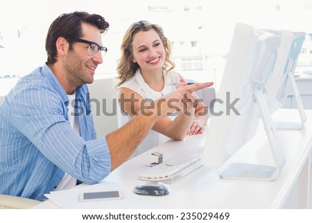 Creative designer talking to his colleague sitting at the desk in office - stock photo