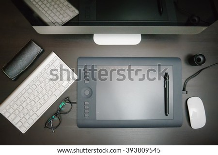 Creative designer workplace with wooden desk table and computer, glasses, supplies, keyboard and mouse, graphic tablet with pen. Top view of modern workplace - stock photo