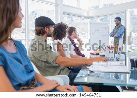 Creative designers sitting in a bright office and listening a presentation - stock photo