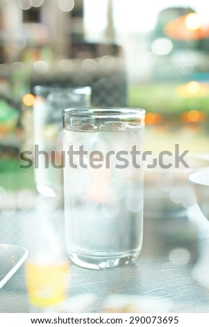 Creative double exposure Glass of drink water in table setting to lunch with blured background