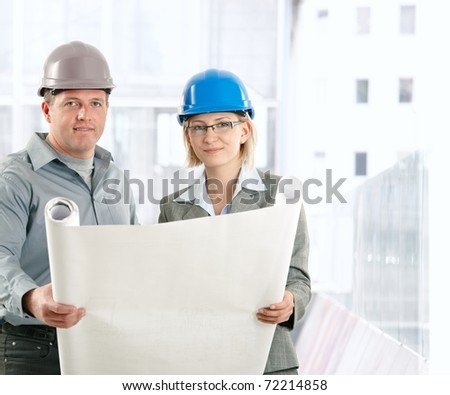 Creative engineer coworkers working on plan in hardhat, smiling at camera.?