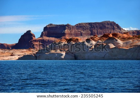 Creative erosion leaves rounded hills of sandstone and giant cliffs of rugged sandstone.  Blue Lake Powell and blue skies frame eroded cliffs. - stock photo