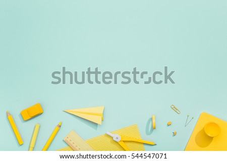 Creative, fashionable, minimalistic, school or office workspace with yellow supplies on cyan background. Flat lay.