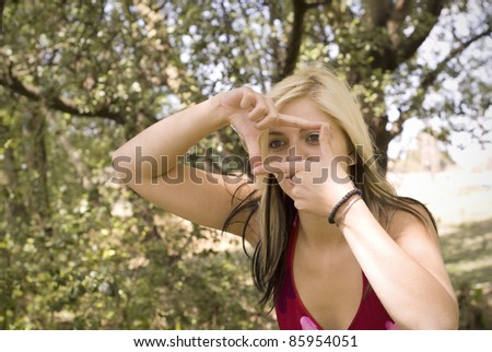 Creative girl or woman photographer framing her photo with finger frame in garden or park - stock photo