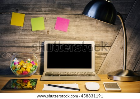 Creative hipster desktop with blank laptop screen, tablet, smartphone, illuminated table lamp and other items. Mock up