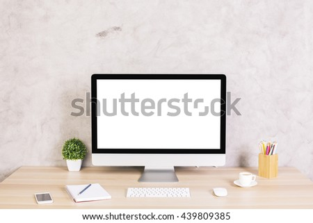 Creative hipster desktop with blank white computer screen, coffee cup, smart phone and other items on concrete background. Mock up - stock photo