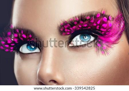Creative Holiday Makeup. False long purple eyelashes closeup. Beauty model woman face make-up with fantasy bright eyelash - stock photo