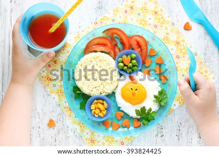 Creative idea for baby morning breakfast. Funny chick egg colorful vegetables fresh tomato juice rice garnish. Concept of healthy food for children top view - stock photo