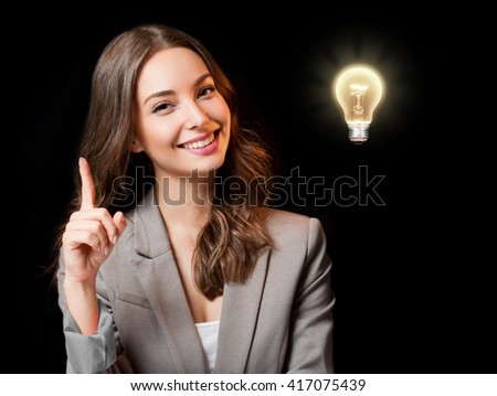 Creative ideas concept, beautiful businesswoman next to glowing light bulb symbol. - stock photo