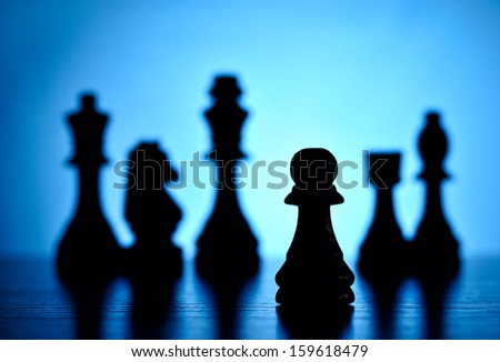 Creative image depicting playing chess with a low angle view of chess pieces on a reflective surface against a graduated blue background with backlighting and focus to a single pawn - stock photo
