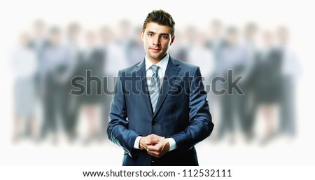 Creative image of attractive businessman in suit with crowd of people on background - stock photo