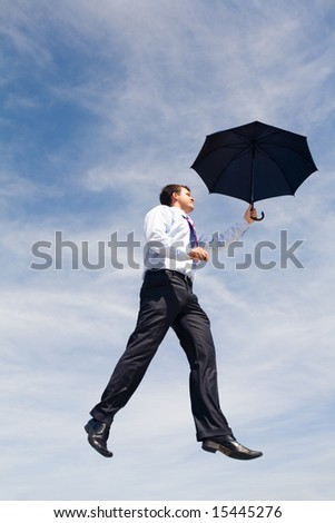 Creative image of businessman with black umbrella flying on the background of sky - stock photo