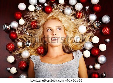 Creative image of lying blond girl with lots of decorative balls on ends of her hair - stock photo