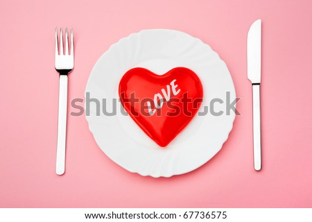 Creative image of valentine heart served on plate with fork and knife near by - stock photo