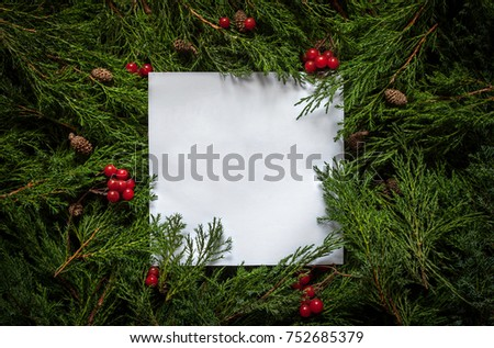 Creative layout made of fir leaves with paper card note. New year flat lay. Nature Christmas concept wallpaper. Concept New Year 2018