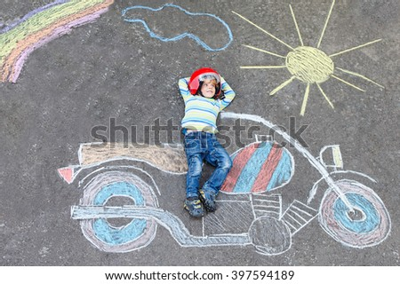 Creative leisure for children: Funny little child of four years in helmet having fun with motorcycle picture drawing with colorful chalks. Children, lifestyle, fun concept. - stock photo