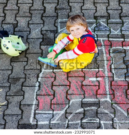 Creative leisure for kids: adorable child of four years having fun with fire truck picture drawing with chalk, outdoors. Dreaming of future profession. Square format. - stock photo