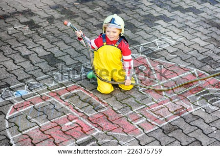 Creative leisure for kids: Funny little boy having fun with fire truck picture drawing with chalk, outdoors - stock photo