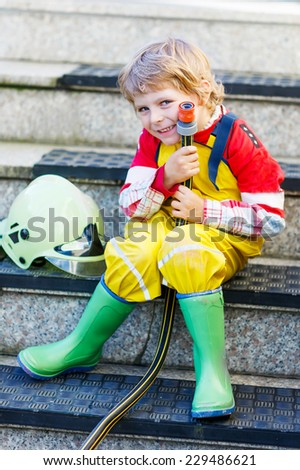 Creative leisure for kids: Funny little child of four years having fun as fireman, in uniform and helmet. - stock photo
