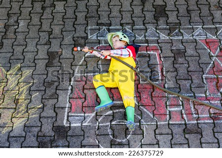 Creative leisure for kids: Little kid boy of four years having fun with fire truck picture drawing with chalk, outdoors. Dreaming of future profession. - stock photo