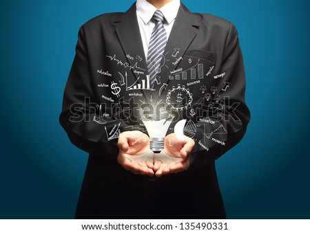 Creative light bulb with drawing business strategy plan concept idea, in the hands of businessmen - stock photo