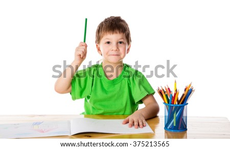 Creative little boy at the table with pencils, pointing up, isolated on white