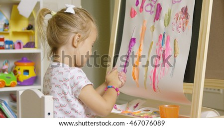 Creative little girl painting an abstract picture