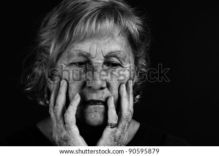 Creative low key black and white to emphasize dramatic facial expression of senior woman. - stock photo