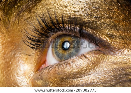 Creative make-up technique: golden paint, macro shot