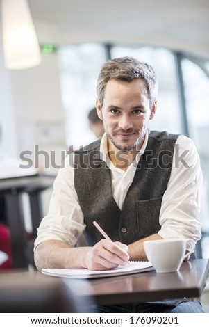 creative man writing in a cafe - stock photo