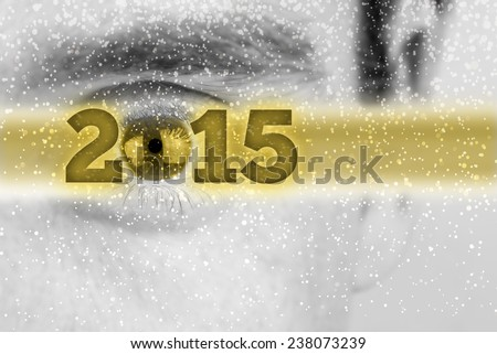 Creative 2015 New Year background with the date in a golden banner superimposed over a greyscale face of a man with the eye forming the 0 in the date and falling snow flakes with copyspace. - stock photo
