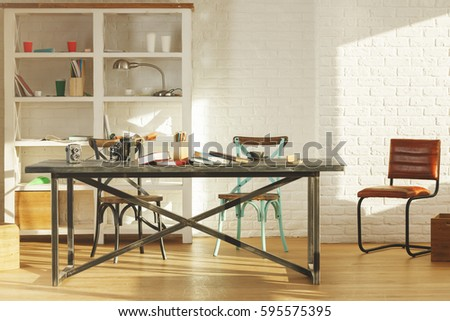 Creative office interior with items on shelves, laptop on table, other items, equipment and sunlight