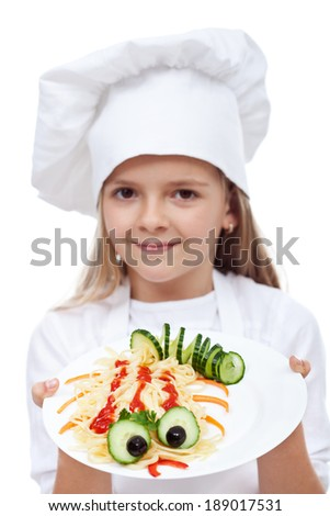 Creative pasta dish with cucumber creature on the side - held by child chef, isolated - stock photo