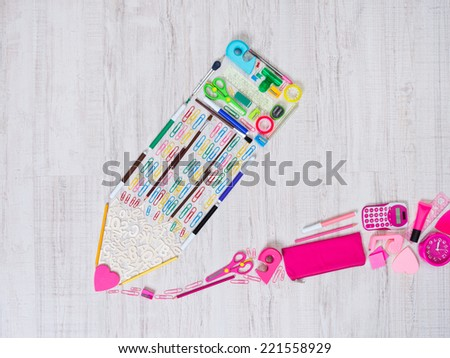 Creative pencil composed of colorful stationery items on the floor. - stock photo