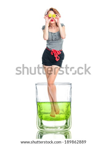 Creative photo of a young woman standing in glass beaker of lemon juice. Girl holding lime over their eyes, isolated on white - stock photo