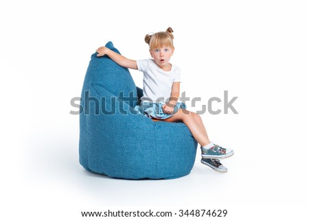 Creative photo of cute little girl isolated on white background. Surprised girl sitting on big frameless chair - stock photo