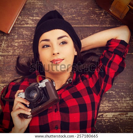 Creative photographer. Top view of beautiful young woman in headwear lying on the floor and holding camera while suitcase and note pad laying near her - stock photo