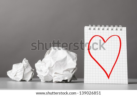 creative process. crumpled wads and notebook with heart picture - stock photo
