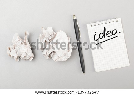 creative process. crumpled wads and notebook with idea word - stock photo