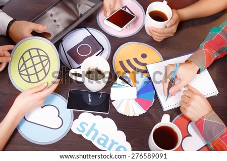 Creative process. Hands of four people holding cup smartphone tablet icon and writing notes in a notebook on the table with pallet  - stock photo
