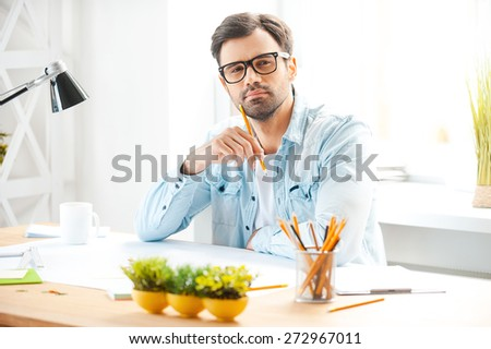 Creative professional at work. Handsome young man in shirt and eyewear holding pencil near his chin and looking at camera while sitting at his working place - stock photo