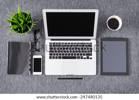 Creative professional's work items and tech gadgets from above - stock photo