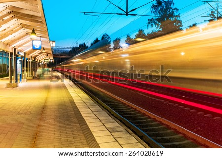 Creative railroad travel and transportation industry business concept: summer evening view of high speed commuter passenger train departing from railway station platform with motion blur effect - stock photo