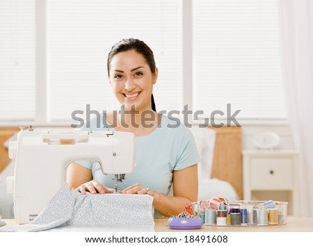 Creative, self-sufficient woman using sewing machine to make clothing - stock photo