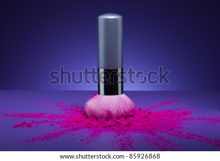 Creative shoot of makeup brush and face powder scattered to all sides from brush - stock photo