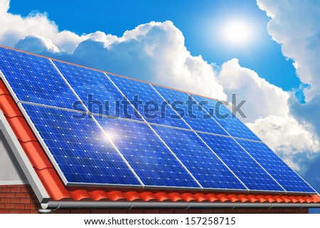 Creative solar power generation technology, alternative energy and environment protection ecology business concept: solar battery panels on red house tiled roof against blue sky with sun light