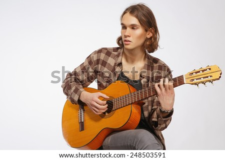 Creative soul. Handsome young guitar player playing acoustic guitar while sitting against white background