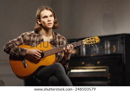 Creative soul. Handsome young sensual man in checked shirt playing acoustic guitar while sitting against the loft room with a vintage piano - stock photo